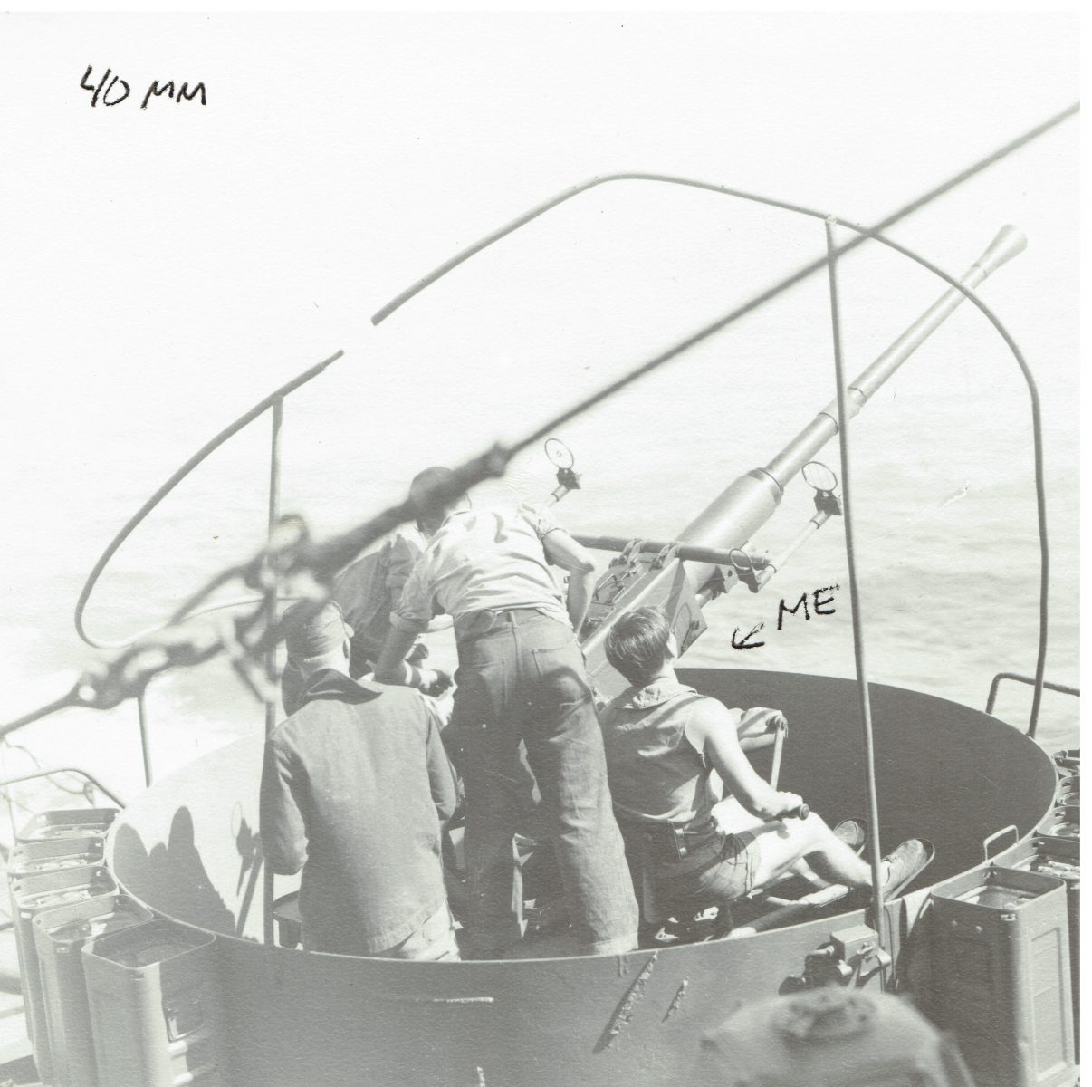 Radioman Second Class Roland Hetfeld (far right) looking down the barrel of a 40 mm anti-aircraft gun during crew training.
