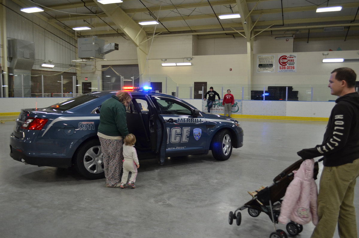 Prominetly displayed with lights flashing, a MPD squad car sits with the back doors open, allowing kids to see what it is like inside.  Hopefully this is the only time they ever see the inside!